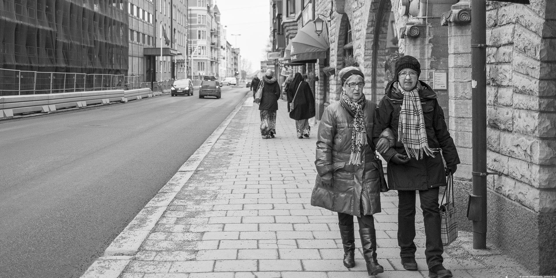 Två damer, arm i arm på gata, svartvitt