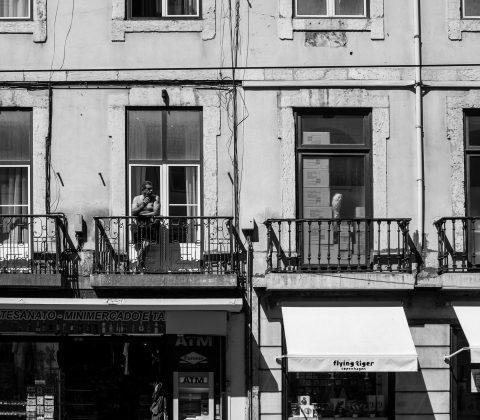 En man på en balkong i Lissabon står och röker|©Jan Andersson